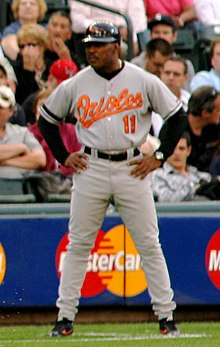 A dark-skinned mustachioed man wearing a gray baseball uniform with orange script across the chest and standing with arms akimbo