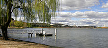 A small pontoon juts out onto the lake under the shade of a tree. Clouds are present in the sky.