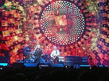 Robert Plant singing and Jimmy Page playing guitar in front of a large screen displaying an elaborate design.