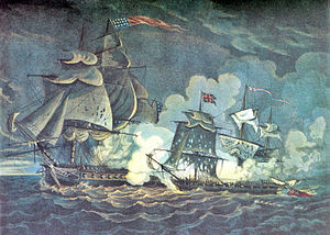 A painting of two sailing ships engaged in battle. The battle occurs in darkness. To the right of the frame a small ship is seen with many holes in its sails from cannon fire. To the left of the frame a much larger ship is firing toward the smaller ship.