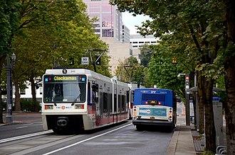 MAX Green Line - A two-car train alongside a TriMet bus on Southwest 5th Avenue of the Portland Transit Mall