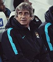 Una fotografía de un señor de unos 60 años.  Él está sentado en un banco del lado rojo.  Él está usando una chaqueta con capucha de color azul marino con una cresta Manchester City en el pecho izquierdo y un logotipo blanco del patrocinador Nike en el pecho derecho.