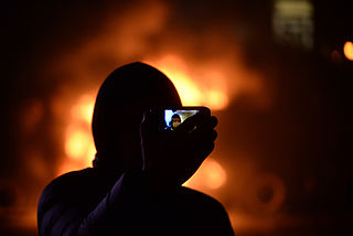 Masked protester taking jis self portrait against background of barricades on fire. Dynamivska str. Euromaidan Protests. Events of Jan 19, 2014.jpg