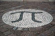 Una fotografía de la letra griega pi, creada como un gran mosaico de piedra incrustado en el suelo.
