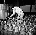 Melkfabriek man vult de melkbussen, Bestanddeelnr 252-9450.jpg
