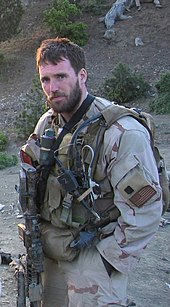 Michael Murphy in tan and brown desert camouflage looking at the camera. He is wearing several pieces of green military combat gear and is holding a weapon. There is a hill behind him covered in rocks, dirt and sticks.