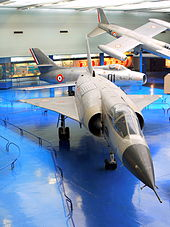 Slightly-angled front view of jet aircraft on blue floor in museum. Two aircraft are in the background, one of which is suspended near the ceiling.
