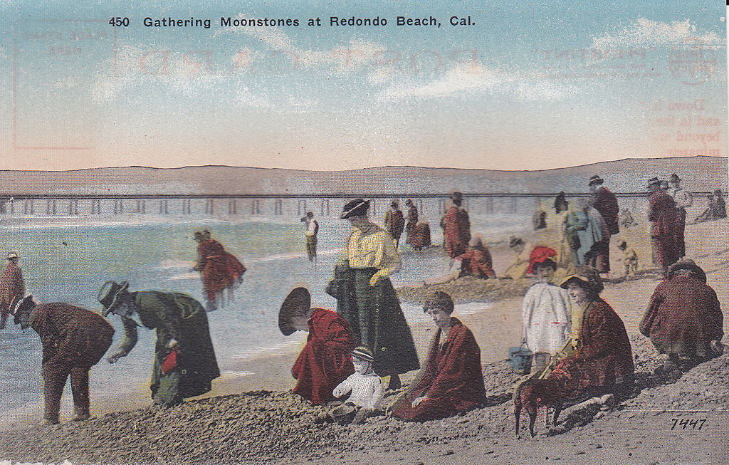 Tourists dressed in 1910 attire picking up moonstones on beach