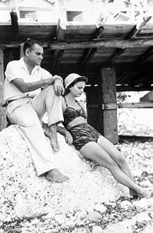 Elsa Morante is leaning against a large rock with Alberto Moravia sitting on the rock, at the beach in Capri, 1940s