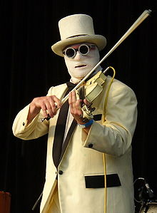 A black background. In the foreground, a man in a white suit with black lapels and black pocket flap, wearing a white top-hat and glasses with a thick circular frame plays an electric violin which is nestled under his left cheek. His face is covered by a layer of surgical bandages, with only a portion of his forehead exposed and a slit at the mouth. A yellow wire hangs from the top of the violin at his left shoulder.