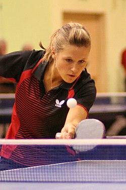 Atleta loira veste camisa vermelha e preta e, segurando uma pequena raquete, olha atentamente para a bola, que passa sobre a rede colocada no meio de uma mesa azul.