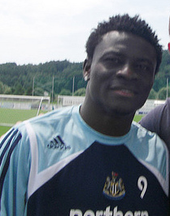Head and upper torso of a young black man wearing a sports shirt with a number nine on the chest.