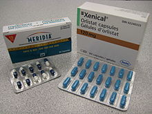 The cardboard packaging of two medications used to treat obesity. Orlistat is shown understanding under the brand name Xenical in a white package with the Roche logo in the bottom right corner (the Roche name within a hexagon). Sibutramine is below under the brand name Meridia. The package is white on the top and blue on the bottom separated by a measuring tape. The A of the Abbott Laboratories logo is on the bottom half of the package.