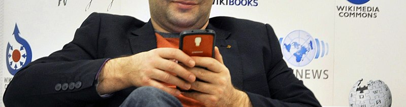 A person holds a mobile phone; in the background are Wikimedia project logos