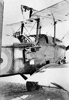 Aviator in military biplane with camera mounted on fuselage