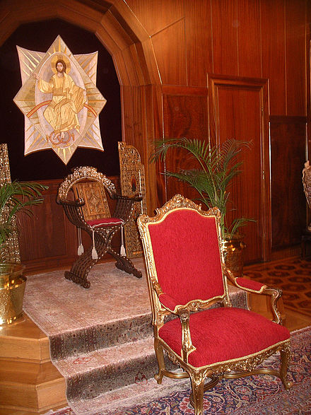 Throne room inside the Patriarchate of Constantinople. The Gospel is enthroned on the dais; the patriarch sits on the lower throne in front. Patriarch of Constantinople throne.jpg