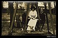 Photographic postcard of a two young men and a woman on a wooden swing (10255445273).jpg