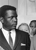 Black and white photo of Sidney Poitier in 1963--a black man about 33 years of age wearing a suit.