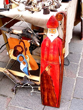 Saint Nicholas Day - A depiction of Saint Nicholas with his sack standing next to a Nativity Scene