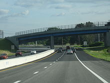 Ground-level view of a divided four-lane freeway; directly in front a large, curved bridge crosses over the freeway.