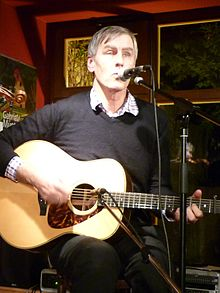 Three-quarter shot of a 55-year-old man sitting on a chair, he is singing into a microphone and playing his guitar. The guitar also has a microphone. He wears dark clothes and has short hair.