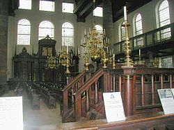 Interior of the Esnoga synagogue in Amsterdam. The tebáh (reader's platform) in the foreground, and the Hekhál (Ark) is in the background.