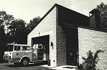 A one-bay firehouse with a white firetruck exiting