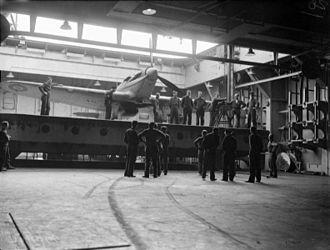 HMS Avenger (D14) - Inside the hangar of HMS Avenger, a lift brings down a Sea Hurricane of 802 Naval Air Squadron.
