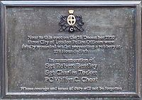"Oblong, brown plaque bearing the words ""Near to this spot on the 16 December 1910 three City of London Police Officers were fatally wounded whilst preventing a robbery at 199 Houndsditch. In commemoration of Sgt Robert Bentley, Sgt Charles Tucker, PC Walter C Choat whose courage and sense of duty will not be forgotten."""