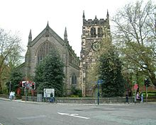 A stone church seen from the west; on the left is the nave with a large Perpendicular window, and on the right is the tower with corner pinnacles