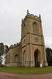 A stone church seen from the northwest, with a tower containing a porch in the foreground, and embattled body of the church stretching behind it