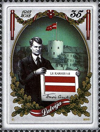 Flag of Latvia - Stamp commemorating the centenary of the Latvian flag, with Ansis Cīrulis holding his design.