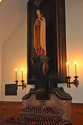 An image of a religious statue of a woman surrounded by candles