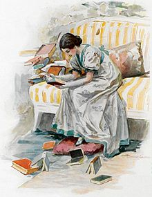 A girl in a gray satin dress sits on the edge of a sofa with large orange and white stripes, her body leaning forward, her naked forearms resting on her thighs. She reads a book she holds in her hands. Around her other books are scattered.