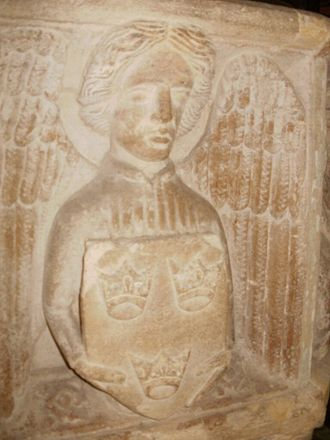 Saxmundham - Carving of an angel holding a Three Crowns emblem on the baptismal font (c.1400) in the parish church of St John the Baptist; the crowns are a symbol of East Anglia.