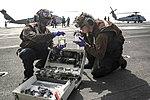 Two Navy Airmen test fuel samples on the flight deck of USS Abraham Lincoln (CVN-72).jpg