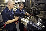 U.S. Navy Aviation Machinist's Mate 2nd Class Dino Tobia, left, and Aviation Machinist's Mate Airman Apprentice Saxton Dees work on an aircraft engine in the jet shop aboard the aircraft carrier USS 130730-N-IB033-094.jpg