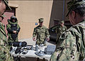 U.S. Navy Explosive Ordnance Disposal Technician 1st Class Matthew Martin, center, assigned to Explosive Ordnance Disposal Mobile Unit (EODMU) 6, presents gear to Vice Adm. John W. Miller, right, the commander 130326-N-LX571-094.jpg