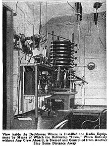 Black and white picture of a cabin. In a corner, intricate apparatus is mounted on a wall above a desk