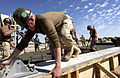 US Navy 030216-N-3783H-445 Builder 2nd Class Adam Turney of Mobile Construction Battalion One Three Three (NMCB-133) pulls a screed across the surface of a concrete pad.jpg
