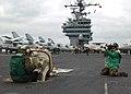 US Navy 031211-N-1082Z-001 Photographer's Mate Airman Joan Kretschmer, of Panama City, Panama, photographs a sailor checking aircraft catapult launch data.jpg