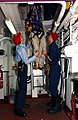 US Navy 040403-N-1082Z-093 Damage Controlman 1st Class Louis Cragg, of Casper, Wyo., and Hull Maintenance Technician 3rd Class Robert Randall, of Beallsville, Ohio, guide a mannequin through an escape trunk during a deep void r.jpg