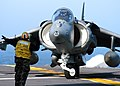 US Navy 050110-N-5313A-082 Aviation Boatswain's Mate Handler 2nd class Esley Smith from Trenton, N.J., directs an AV-8B Harrier to turn right.jpg