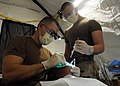 US Navy 090209-N-1120L-066 Lt. Matthew Dart, left, a dental officer assigned to Naval Mobile Construction Battalion (NMCB) 7, and Hospital Corpsman Mark Lunde replace a filling at a forward operating base.jpg
