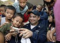 US Navy 090424-N-9520G-237 Machinist's Mate Timothy Walker, from Houston, Texas assigned to the amphibious assault ship USS Essex (LHD 2), shows photos on his digital camera to students at Banicain Elementary School.jpg