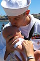 US Navy 090806-N-6031Q-001 A Sailor assigned to the Los Angeles-class attack submarine USS Albuquerque (SSN 706) kisses his baby as he arrives in San Diego.jpg