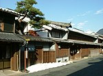 Two storied traditional Japanese houses next to a street.