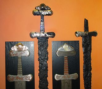 Viking sword - Two 10th-century sword hilts (Petersen type S) with Jelling style inlay decorations, with replicas, on display in Hedeby Viking Museum.