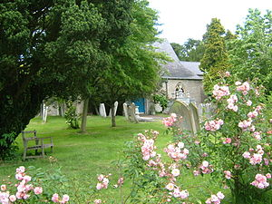 Wateringbury - The churchyard of St John the Baptist with a yew, roses, a sundial and monuments