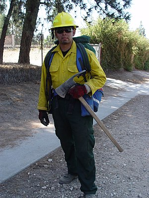 Wildfire suppression equipment and personnel - Holding a Pulaski, a wildland firefighter from the Angeles National Forest responds to a fire in Altadena, California on July 9, 2006.